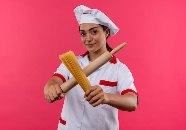 Jovem plesed caucasiana cozinheira com uniforme de chef cruza o rolo de massa e um monte de espaguete isolado na parede rosa com espaço de cópia