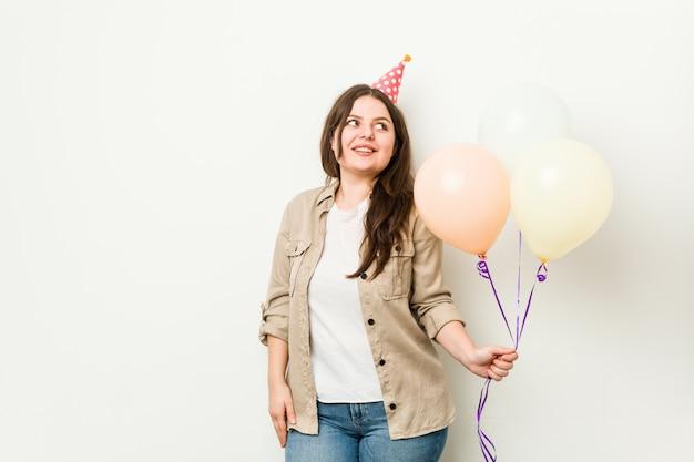 Jovem plus size mulher curvilínea comemorando um aniversário parece de lado sorrindo, alegre e agradável