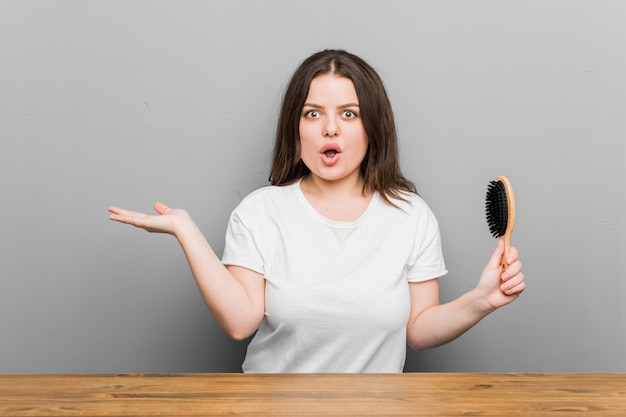 Jovem plus size mulher curvilínea segurando uma escova de cabelo impressionado