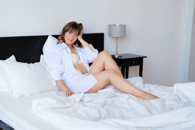 Jovem, plus size, mulher, em, roupa interior, e, camisa, cama, em, hotel