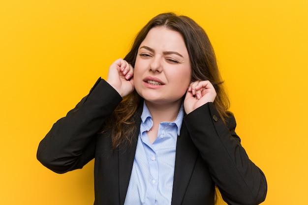 Jovem plus tamanho mulher de negócios caucasiano cobrindo as orelhas com as mãos.