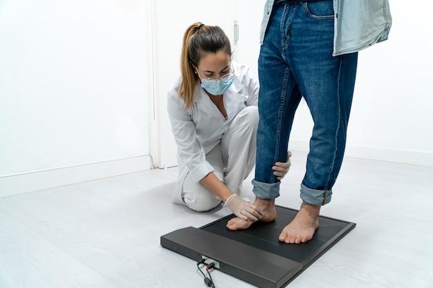 Jovem podólogo examinando os pés de um paciente em uma plataforma de pressão