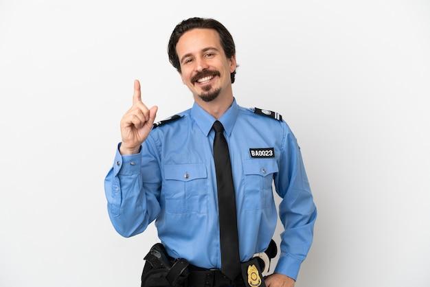Jovem policial sobre fundo branco isolado mostrando e levantando um dedo em sinal dos melhores