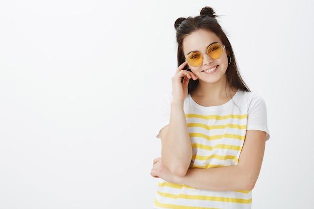 Jovem posando com óculos de sol contra uma parede branca