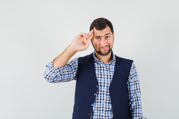 Jovem posando com os dedos apontados para a cabeça na camisa, colete e parecendo confiante.