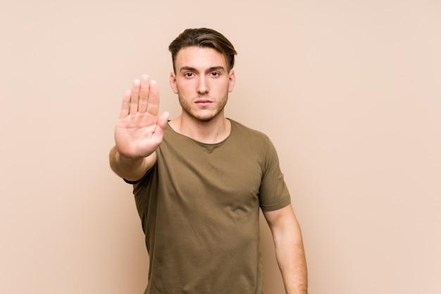 Jovem posando em pé com a mão estendida, mostrando o sinal de stop, impedindo-o