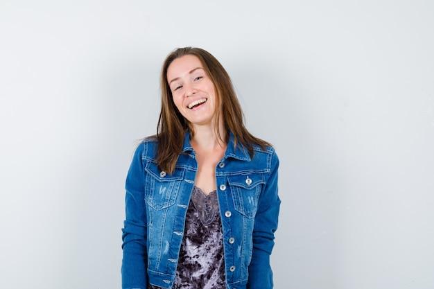 Jovem posando em pé com uma blusa, jaqueta jeans e parecendo feliz. vista frontal.