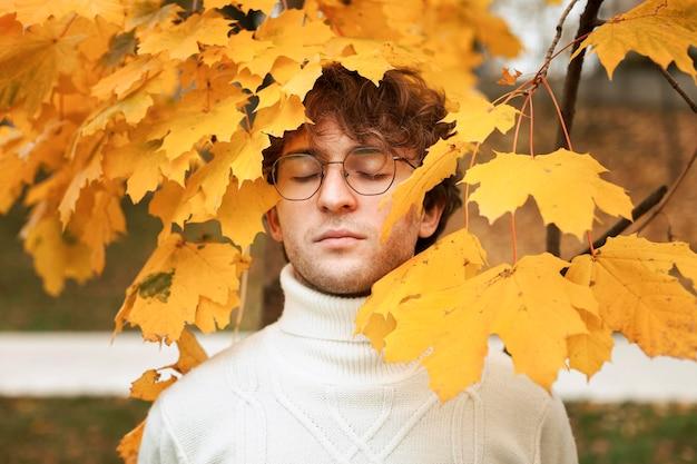 Jovem posando nas folhas de outono