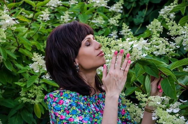 Jovem posando perto de uma árvore em flor
