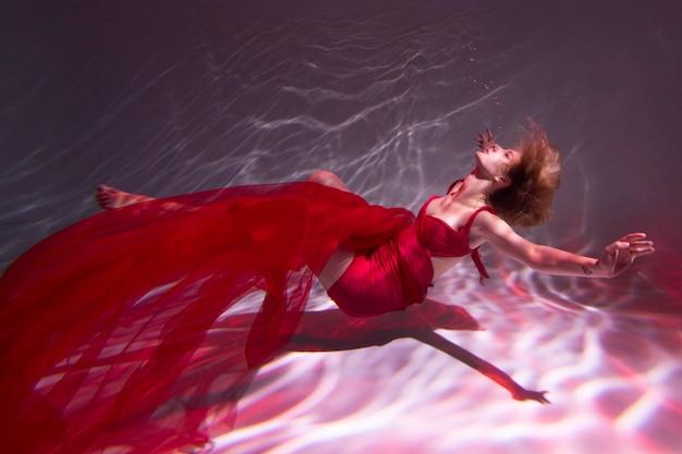 Jovem posando submersa na água com um vestido esvoaçante Foto gratuita