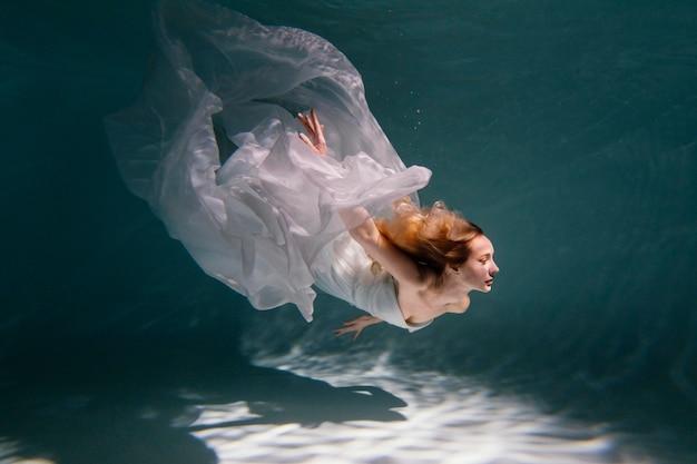 Jovem posando submersa na água com um vestido esvoaçante