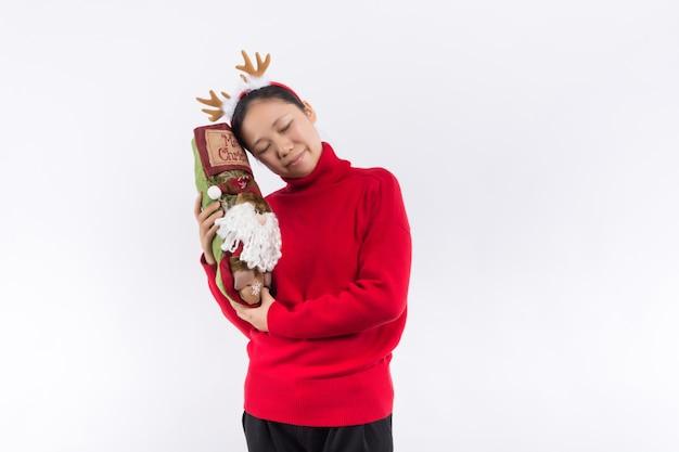 Jovem positiva animada em traje vermelho de papai noel com capuz segurando caixas de presentes e usando smartphone isolado