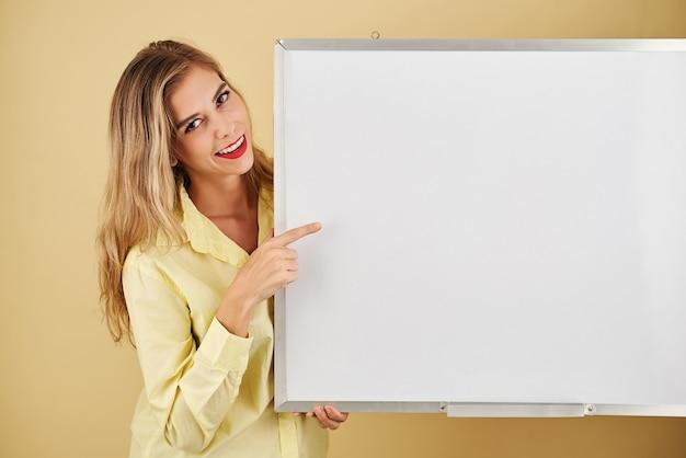 Jovem positiva apontando para um quadro branco vazio e sorrindo