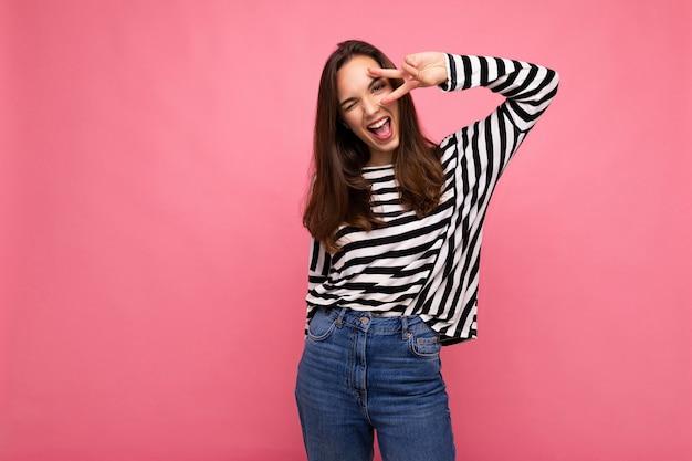 Jovem positiva cativante feliz linda mulher morena com emoções sinceras, vestindo pulôver listrado casual, isolado no fundo rosa com espaço de cópia.