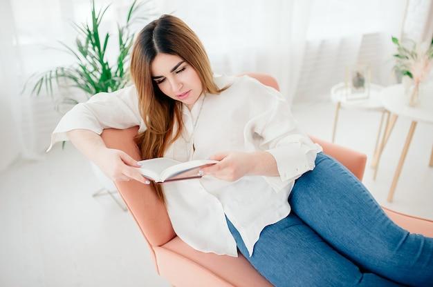 Jovem positiva em uma camisa branca e calça jeans lê um livro enquanto estava deitado em uma cama em casa, quarto aconchegante e brilhante. educação escolar em casa