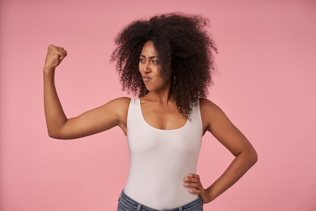 Jovem positiva encaracolada com pele escura posando em rosa com camisa branca e jeans, olhando para a mão levantada enquanto demonstrava alegremente seus fortes bíceps