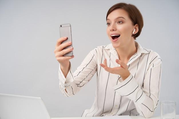 Jovem, positiva, morena, de cabelos curtos, com penteado casual, levantando emocionalmente a palma da mão e sorrindo amplamente enquanto conversa por vídeo com seu telefone celular