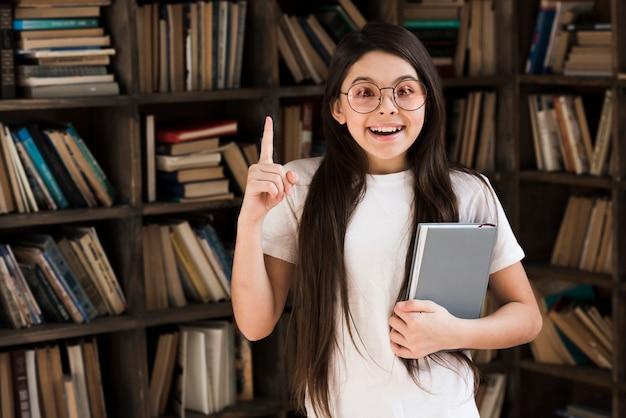 Jovem positiva, segurando um livro na biblioteca