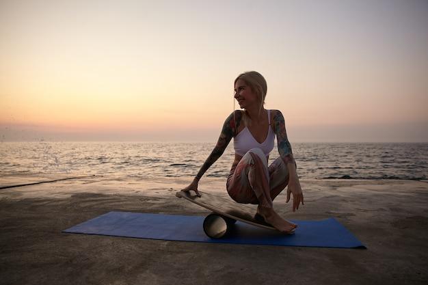 Jovem positiva tatuada em boas condições físicas posando com vista para o mar, sentada no colchonete e apoiada na prancha de equilíbrio, praticando esportes no início da manhã à beira-mar