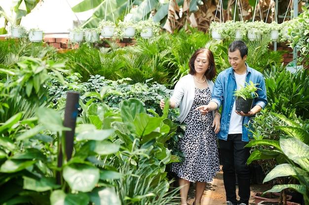 Jovem positivo ajudando o cliente a escolher boas flores e plantas para o jardim de seu quintal