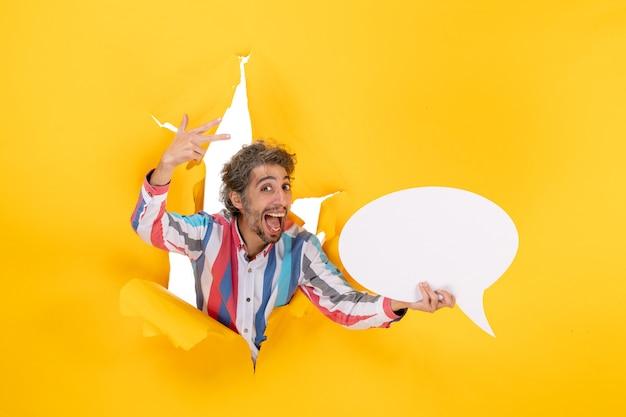 Jovem positivo apontando uma página em branco com espaço livre em um buraco rasgado em papel amarelo