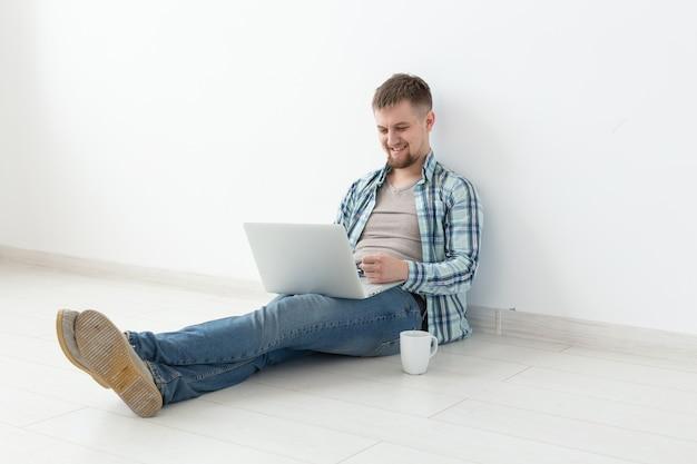 Jovem positivo com roupas casuais e óculos, navegando na internet usando wi-fi e um laptop em