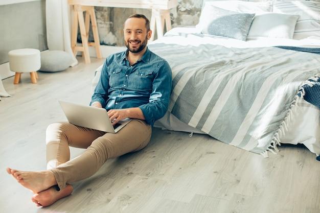 Jovem positivo ficando em casa e sorrindo enquanto trabalha no laptop em seu quarto