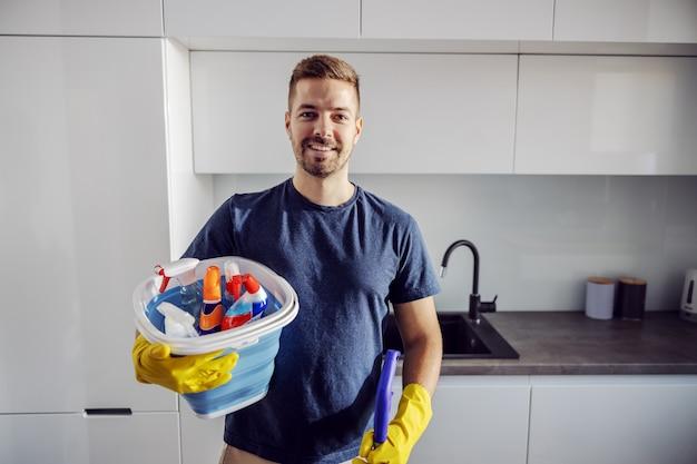 Jovem positivo sorridente digno barbudo em pé em casa com um balde cheio de produtos de limpeza e se preparando para limpar a casa inteira.
