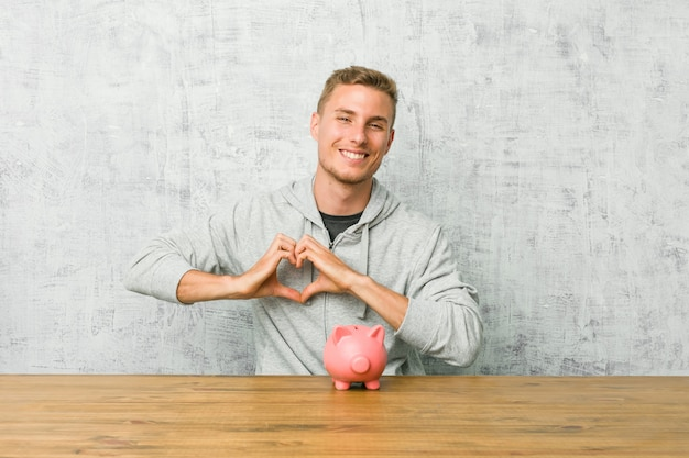Jovem, poupar dinheiro com um cofrinho, sorrindo e mostrando uma forma de coração com as mãos.