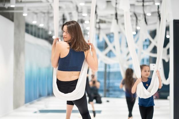 Jovem pratica ioga aérea antigravitante