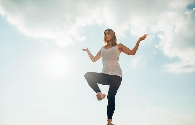 Jovem pratica ioga do lado de fora. rapariga loira em pé em uma perna, outra dobrada no joelho levantada mãos nas laterais dobradas nos cotovelos e voltadas para cima. céu e nuvens