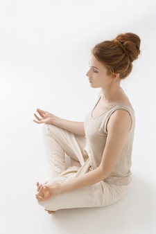 Jovem pratica ioga em fundo branco. retrato de uma linda mulher de cabelo ruivo caucasiano fazendo