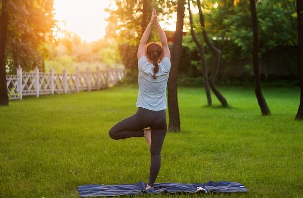 Jovem pratica ioga no parque em um gramado verde.