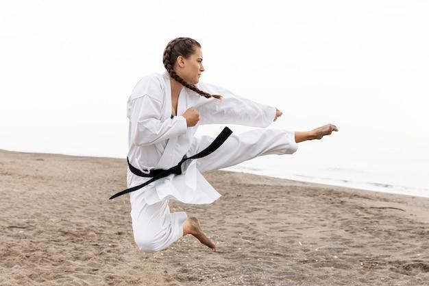 Jovem praticando arte marcial ao ar livre
