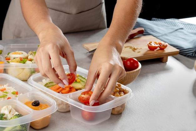 Jovem praticando cozimento em lote com alimentos saudáveis