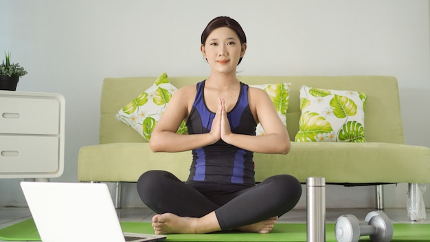 Jovem praticando ioga com foco em casa