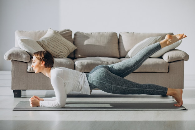 Jovem praticando ioga em casa no tapete