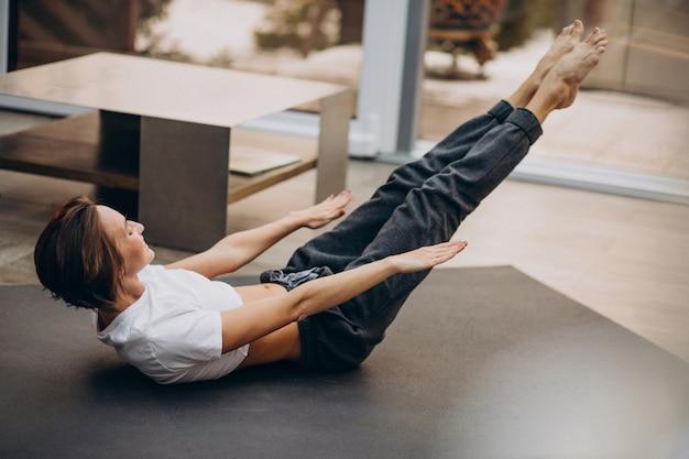 Jovem praticando ioga em casa
