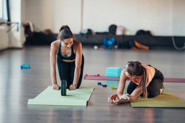 Jovem praticando ioga, está envolvida com o professor online.
