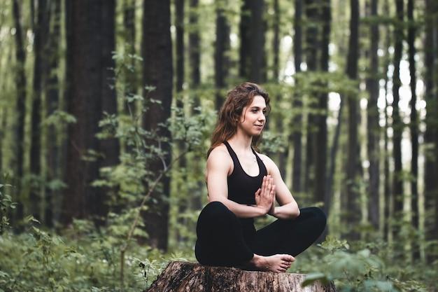 Jovem praticando ioga na floresta, o conceito de desfrutar de privacidade e concentração, luz do sol