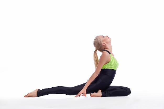 Jovem praticando ioga, sentada no chão, esticando as costas