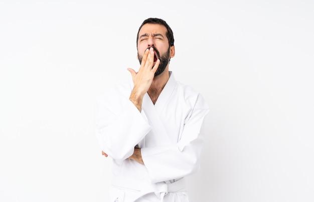 Jovem praticando karatê sobre bocejar branco isolado e cobrindo a boca aberta com a mão