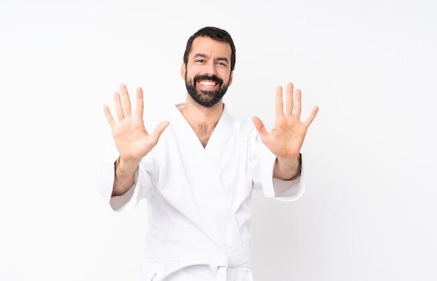 Jovem praticando karatê sobre branco isolado, contando dez com os dedos