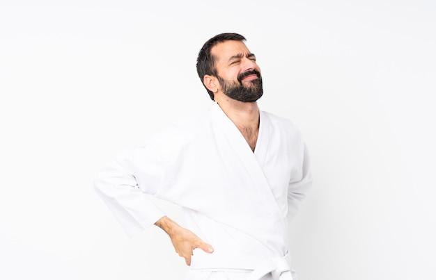 Jovem praticando karatê sobre fundo branco isolado, sofrendo de dor nas costas por ter feito um esforço