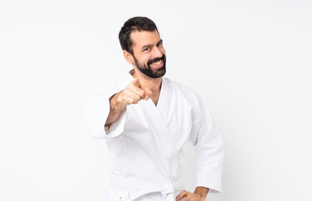 Jovem praticando karatê sobre pontos isolados dedo para você com uma expressão confiante