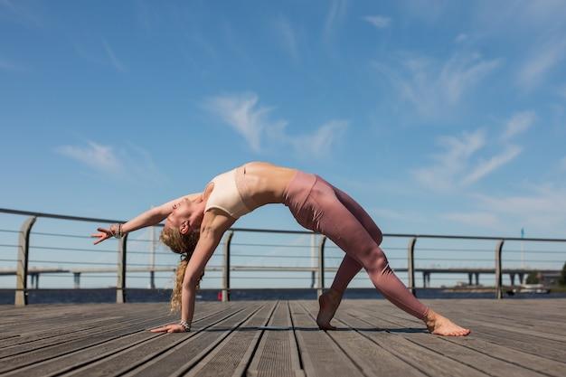Jovem praticando postura de ioga de coisa selvagem no terraço de madeira do calçadão em um dia ensolarado