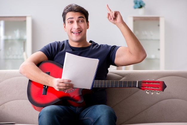 Jovem praticando tocando violão em casa
