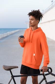 Jovem praticante de esportes ao ar livre na praia com uma bicicleta segurando café
