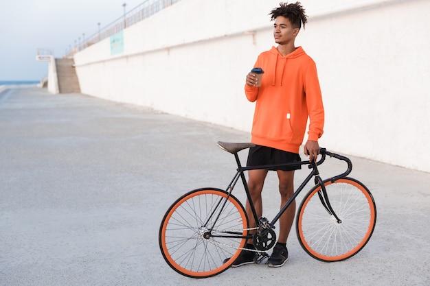 Jovem praticante de esportes ao ar livre na praia com uma bicicleta segurando café Foto Premium