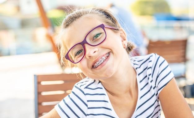 Jovem pré-adolescente de óculos usando aparelho sorri para a câmera em um dia de verão.